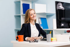 Woman sitting at the desk  with computer Royalty Free Stock Image