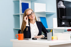 Woman sitting at the desk  with computer Royalty Free Stock Photos