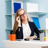 Woman sitting at the desk  with computer Stock Images