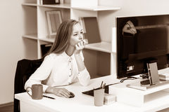 Woman sitting at the desk  with computer Stock Photography