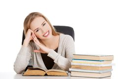 Woman sitting at the desk full of books Stock Images