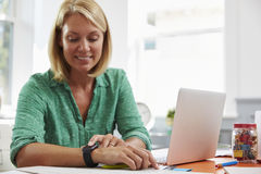 Woman Sitting At Desk In Home Office Looking At Smart Watch Royalty Free Stock Image