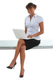 Woman sitting on a desk. With a laptop Stock Images