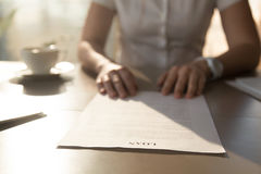 Woman sitting at the desk with loan agreement form. Close up photo of female hands lying on business document. Businesswoman reading  contract terms. Financial Royalty Free Stock Image