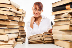 Woman sitting by the desk with pile of books Stock Photos