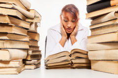 Woman sitting by the desk with pile of books Royalty Free Stock Photography