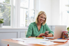 Woman Sitting At Desk Using Mobile Phone In Home Office Royalty Free Stock Image