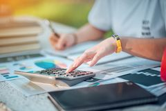 Woman sitting at desk and working at hand of book and financial stock image