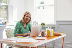 Woman Sitting At Desk Working At Laptop In Home Office Stock Photo