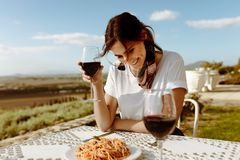 Woman sitting at a dining table drinking wine. Smiling woman sitting at the table in an open air restaurant with a vineyard in the background. Smiling woman on a stock image