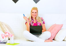 Woman sitting on divan with laptop and credit card Royalty Free Stock Images