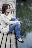Woman sitting on dock near water. Portrait of a young caucasian woman in her 30's sitting on a dock near water royalty free stock image