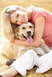 Woman Sitting With Dog On Straw Bales In Harvested Stock Photos