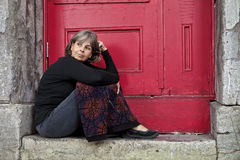 Woman sitting on door stoop Stock Images