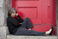 Woman sitting on door stoop Stock Photos