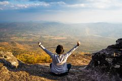 A woman sitting down with hands up on rocky mountain looking out at scenic natural view and beautiful blue sky stock photo