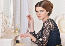 Woman sitting at dressing table with necklace of pearls. Beautiful young woman sitting at dressing table with necklace of pearls royalty free stock images
