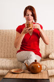 Woman sitting and drinking tea. Stock Image