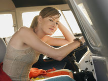 Woman Sitting At Driver's Seat Of Campervan. Portrait of beautiful young woman sitting at driver's seat of campervan stock images