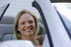 Woman sitting in driving seat of parked convertible car on driveway, smiling, close-up, portrait Stock Photos