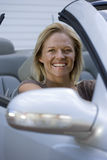 Woman sitting in driving seat of parked convertible car on driveway, smiling, portrait Royalty Free Stock Photos