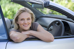 Woman sitting in driving seat of parked convertible car on driveway, smiling, side view, portrait stock photo