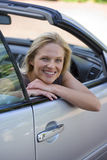 Woman sitting in driving seat of parked convertible car on driveway, smiling, side view, portrait stock images
