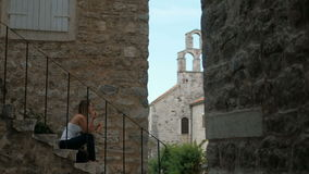 Woman sitting eating on open stairs in old town outdoors. Blond female in white top, black trousers sit in profile eat sweet bun walking on ancient city next stock video footage