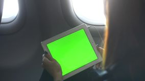 Woman is sitting at economy class and listening music through headset and tablet while jet is getting height. Wireless smart digital technology for work and stock video footage