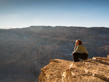 Woman sitting on the edge of a cliff. On the background of mountains Royalty Free Stock Photos
