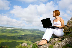 Woman sitting on edge of a cliff with a laptop stock images