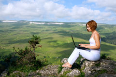 Woman sitting on  edge of a cliff with a laptop Stock Photo