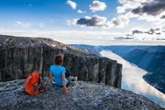 A woman is sitting on the edge of cliff on the way to boulder K Stock Photo