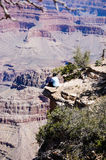 Woman sitting on edge of Grand Canyon Royalty Free Stock Photography