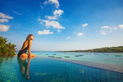 Woman sitting on the edge of infinity pool stock photography