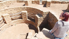 Woman Sitting On The Edge of a Kiva. A woman sits, smiling with her legs dangling over the side of a Kiva at the Mesa Verde National Park stock photo