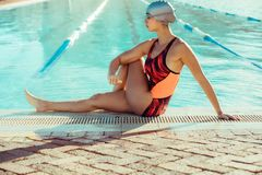 Woman sitting on the edge of pool and stretching Stock Photos