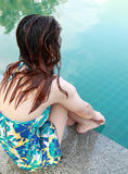 Woman sitting at the Edge of Swimming Pool Stock Photos