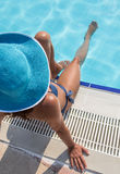 Woman sitting  on a edge of swimming pool. Stock Photo