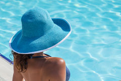 Woman sitting  on a edge of swimming pool. Stock Photography