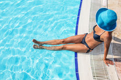 Woman sitting  on a edge of swimming pool. Royalty Free Stock Photo