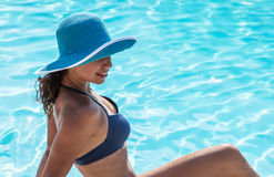 Woman sitting  on a edge of swimming pool. Stock Photos