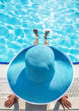 Woman sitting on a edge of swimming pool. Royalty Free Stock Photos