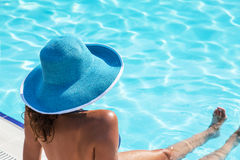 Woman sitting  on a edge of swimming pool. Royalty Free Stock Photography