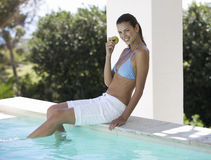 A woman sitting on the edge of a swimming pool eating an apple Stock Photography