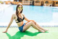 Woman sitting on the edge of swimming pool. Summer time Royalty Free Stock Image