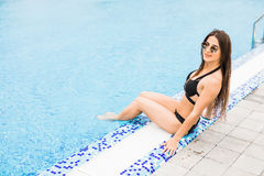 Woman sitting on the edge of swimming pool. Summer time Stock Photos