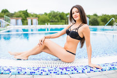 Woman sitting on the edge of swimming pool. Summer vocation Stock Image