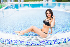 Woman sitting on the edge of swimming pool. Summer vocation Royalty Free Stock Photos