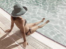 Woman sitting on the edge of swimming pool. Stock Image